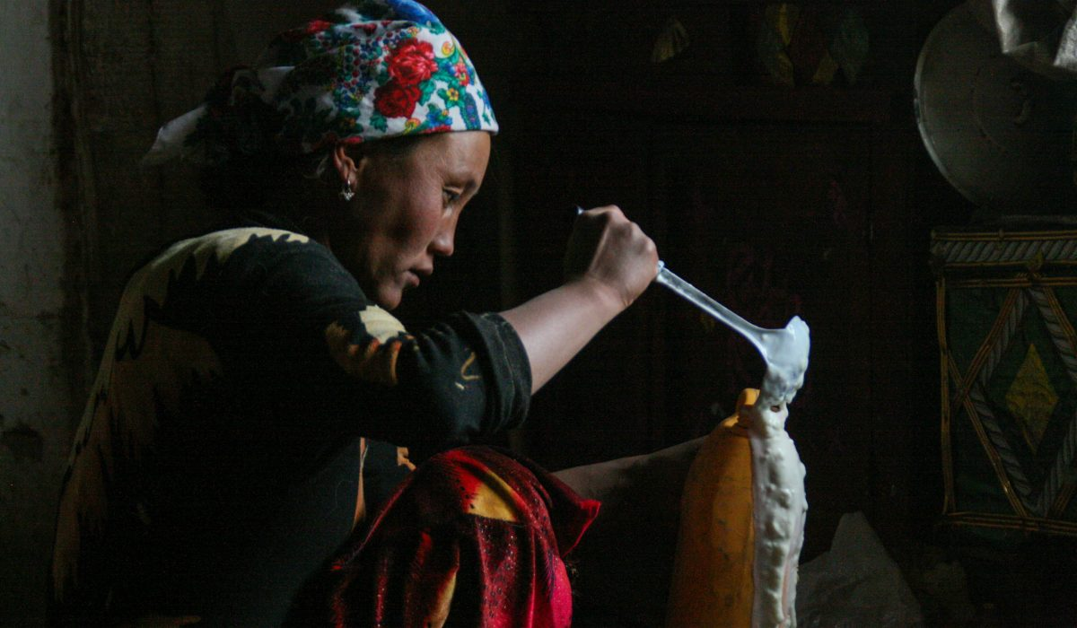 Cara Kerven, In Murghab town, the largest settlement in the eponymously named district in Gorno-Badakhshan Autonomous Region, Tajikistan. Many families lease their livestock to hired shepherds. Here, the wife of a shepherd pours yogurt (ayran) made from yak's milk to take with us back into Murghab town
