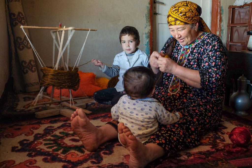 By Cara Kerven - In the Gara Gum desert, Turkmenistan, a grandmother looks after her youngest grandson. In the background, her granddaughter helps spool the yarn, which will then be used to make plaited lengths (alaja) that protect against the evil eye. These alaja are most commonly plaited with four colors,  the brown color often made from undyed camel hair.