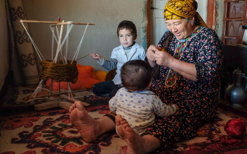 In the Gara Gum desert, Turkmenistan, a grandmother looks after her youngest grandson. In the background, her granddaughter helps spool the yarn, which will then be used to make plaited lengths (alaja) that protect against the evil eye. These alaja are most commonly plaited with four colors,  the brown color often made from un-dyed camel hair.