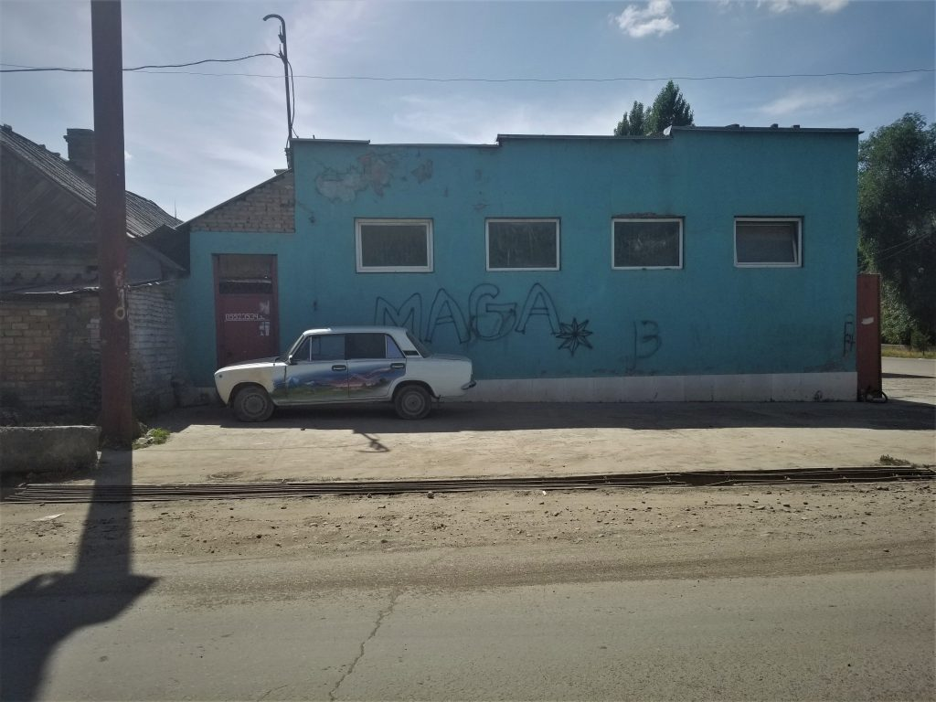 "By Jennifer Murtazashvili, Kyrgyzstan, 2019 - The photo was taken on the outskirts of Jalalabad in June 2019. A blue building has the word ""MAGA"" spray painted on it. I thought this to be an unusual place to find MAGA propaganda. I've spoken to friends from the area to see if the photo may have more local meaning. There was no consensus on this. The juxtaposition of the spray-painted car was also quite interesting."