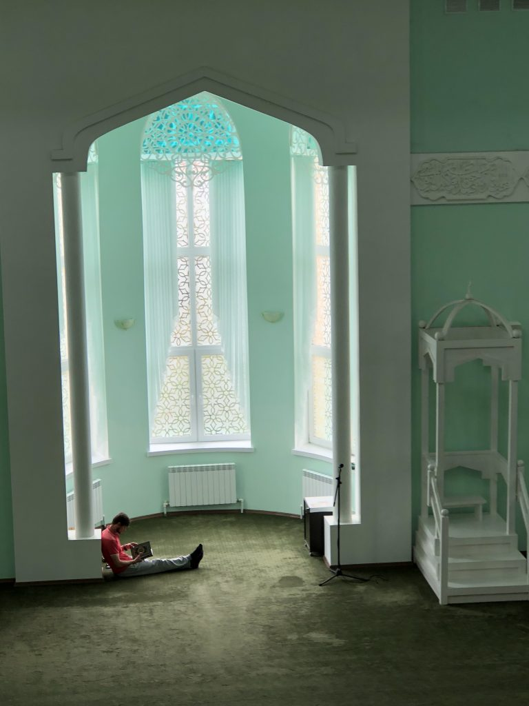 By Liliya Karimova, Tatarstan, Russia, 2018 - I took this photo at a mosque one Saturday afternoon in July 2018 in Tatarstan, Russia. I came to the newly-built mosque in a small town outside of Kazan to meet with a Muslim Tatar woman I wanted to interview. While waiting for the woman in the balcony—the women's prayer section of the mosque—I peeped from behind the vertical blinds that blocked the view from the balcony onto the main floor, themen's section. My female ethnographic gaze fell on a man who settled on the floor with a copy of the Qur'an. While the man could not see me, I could see and photograph him.