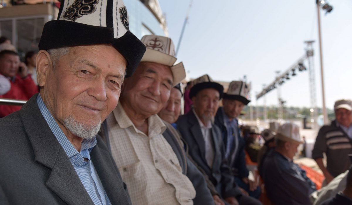 Moira O'Shea, Kyrgyzstan, 2018, This photo was taken during the World Nomadic Games in CholponAta, Kyrgyzstan, 2018. Attending every match of Kok-boru, I became friendly with some of the fans who also watched every match, like this group, some of whom had come from Jalal-Abad together. Sitting with them was an education in the skills and characteristics one needs to become a good Kok-boru player, as well as an opportunity to hear stories about their own adventures, and sometimes misadventures, when playing the game.