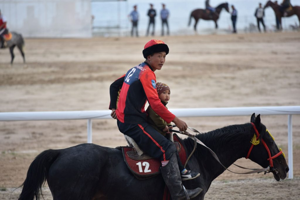 By Moira O'Shea, Kyrgyzstan, 2018 - Research on the history and contemporary form of Kok-boru has led to conversations about the origin of the game, about which country's rules to use in international games, and the mutual understanding between a rider and his horse. One idea that has stood out, however, is the idea that Kok-boru is something that is in the blood and which is not explicitly taught but rather demonstrated. To me, this picture,taken after Kyrgyzstan won the final match during the World Nomadic Games in 2018, illustrates the sharing of knowledge of the game from one generation to the next. Cholpon-Ata, Kyrgyzstan.