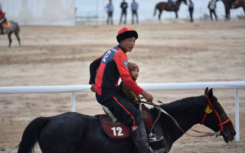 Moira O'Shea, Kyrgyzstan, 2018, Research on the history and contemporary form of Kok-boru has led to conversations about the origin of the game, about which country's rules to use in international games, and the mutual understanding between a rider and his horse. One idea that has stood out, however, is the idea that Kok-boru is something that is in the blood and which is not explicitly taught but rather demonstrated. To me, this picture, taken after Kyrgyzstan won the final match during the World Nomadic Games in 2018, illustrates the sharing of knowledge of the game from one generation to the next. Cholpon-Ata, Kyrgyzstan.