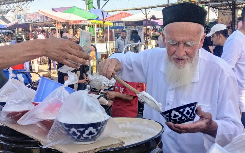 """Rashid Gabdulhakov, Uzbekistan, 2019,  An old man from the fairytale '1001 nights' at Chorsu bazaar in the centre of Namangan. He is captured here selling """"misholda"""" – a local marshmallow-like sweet substance served during the holy month of Ramadan."""