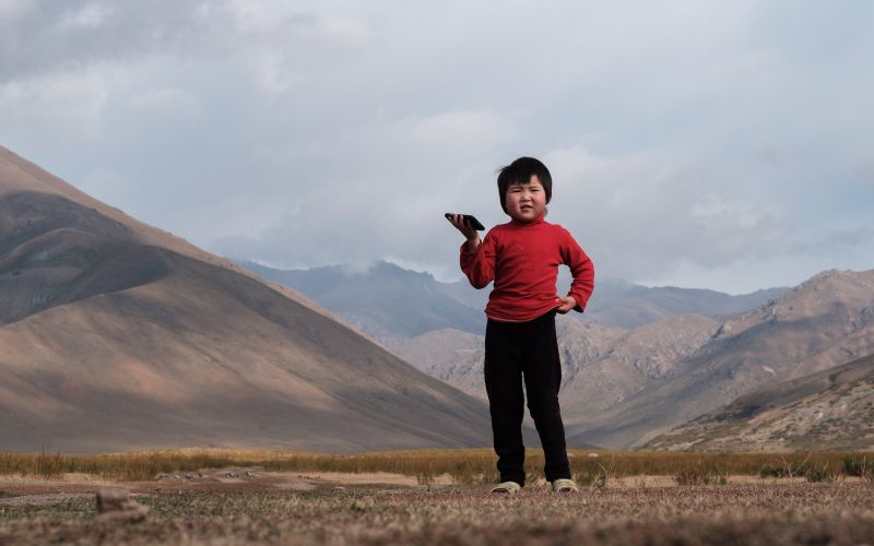 """Talant Sultanov Kyrgyzstan, 2018, Rayana Imankulova (4), pictured on 13 September 2018, lives with her parents Akylbek Imankulov (46) and Gulzat Raimbekova (43) in the rangelands of Tokoilu in the Suusamyr Valley, which lies above 2000m in the Tian Shan Mountains in Kyrgyzstan. She loves to watch cartoons on her parents' smartphone. Before a Suusamyr Net community network repeater tower was erected right next to her family's small corrugated iron home, they had to buy expensive and unreliable mobile data packages that were quickly exhausted. But now the family has free WiFi in exchange for looking after the tower equipment, and Rayana can watch her favorite cartoons non-stop – she particularly loves the Russian series Masha and the Bear. """"The one where the rabbits ate all the carrots and potatoes and Masha had to spank them is the best,"""" she says. However, the new WiFi connection recently stopped working for three days due to an electrical fault and Rayana could not watch her cartoons. """"There was no WiFi so I threw pillows around!"""" she says, pouting. [Photo: Nyani Quarmyne / Text: Laura Salm-Reifferscheidt]"""